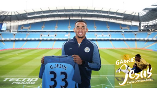 a9440bc0e Gabriel Jesus holds up his City shirt with the Etihad Stadium pitch in the  background