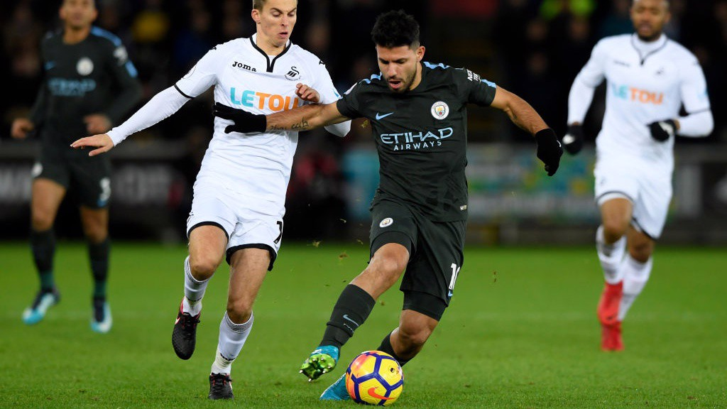 ON THE BALL: Sergio Agüero holds off Swansea's Tom Carroll in the middle of the park.